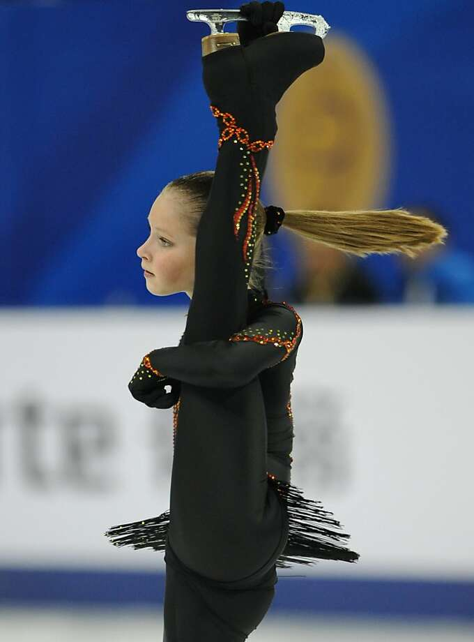 Perpendicular ponytail: Seemingly defying the laws of anatomical physics, Julia Lipnitskaia of Russia lifts one leg over her head while gliding upright on the other during her short program routine at The Cup of China in Shanghai. Photo: Peter Parks, AFP/Getty Images