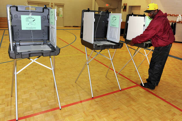 Henry Stanley sets up voting booths in the gymnasium at Dunbar School, in Bridgeport, Conn. Nov. 5th, 2012. Photo: Ned Gerard / Connecticut Post