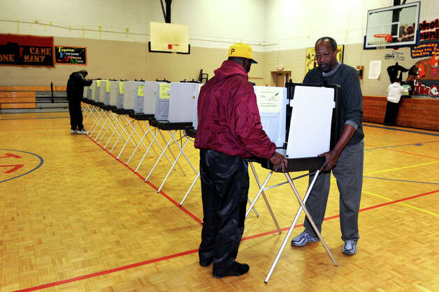 Henry Stanley, left, and Ralph Bowen set up voting booths in the gymnasium at Dunbar School, in Bridgeport, Conn. Nov. 5th, 2012. Photo: Ned Gerard / Connecticut Post