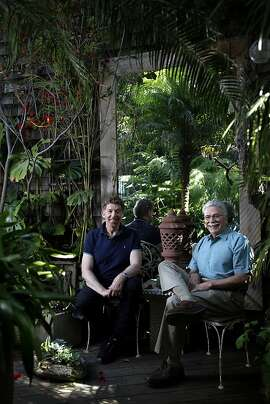 Richard Gervais, right, and Chris Jacobson relax in their urban oasis of a garden in SoMa in San Francisco, Calif., Wednesday, October 3, 2012.  Gervais has transformed the outdoor space into a lush tropical paradise over the last 17 years.