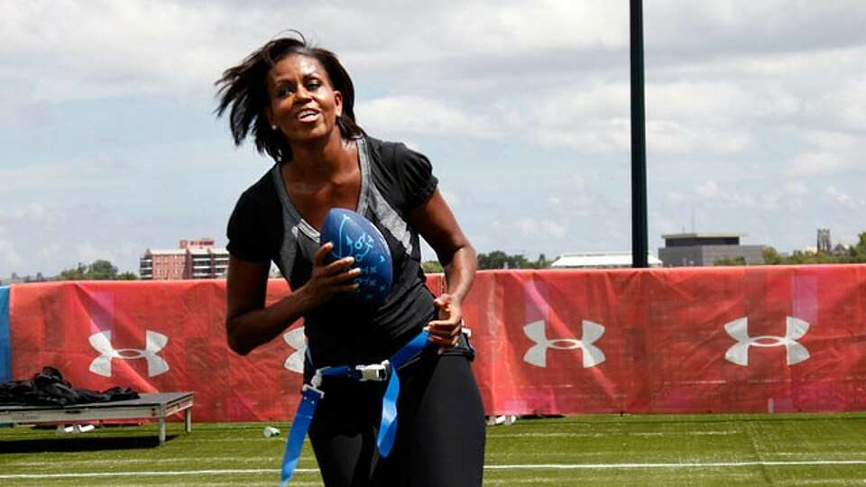 First lady Michelle Obama turns and runs after catching a pass while participating in the Let's Move