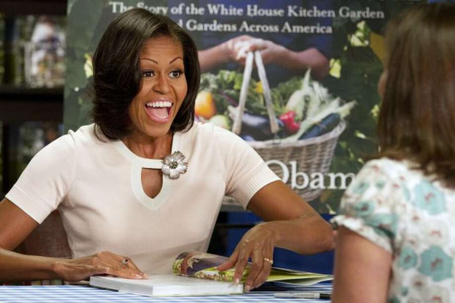 "First lady Michelle Obama signs copies of her book ""American Grown: The Story of the White House Kitchen Garden and Garden Across America,"" in Washington, Tuesday, June 12, 2012.  (Jacquelyn Martin / AP Photo)"