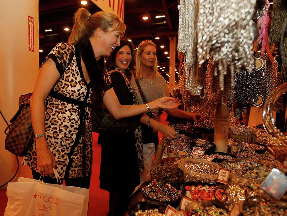 Emily Edmonds, left, Lisa Matus, center, and Mandi Rouhselang, right, shop at the Art by Amy booth at the Nutcracker Market Preview party at Reliant Center, Nov. 9, 2011. ( Karen Warren / Houston Chronicle ) Photo: Karen Warren, Staff / © 2011 Houston Chronicle