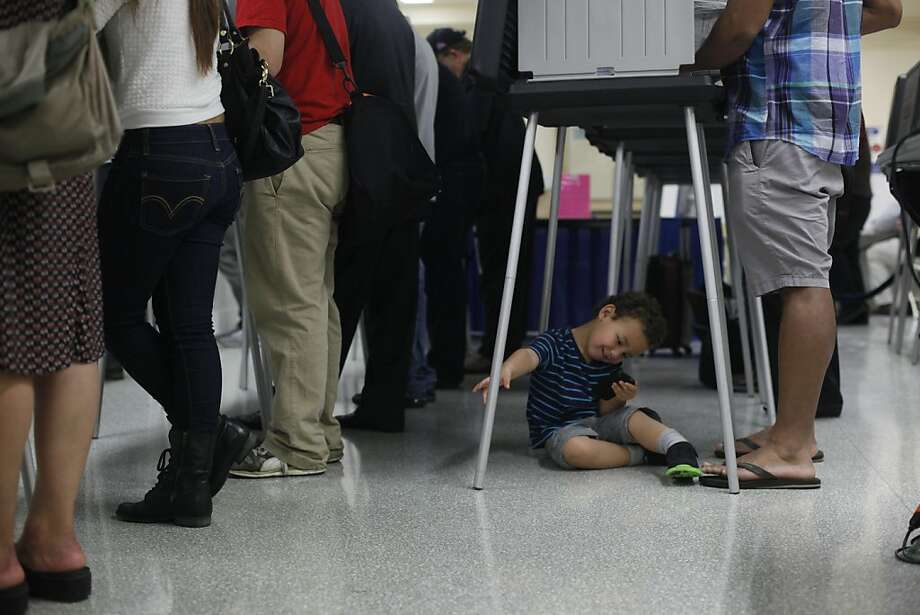 Atticus Muse, 3, waits on the floor while his dad, Maurice Muse, fills out his ballot with other early voters at San Francisco City Hall. Tuesday is the final day to vote on national, state and local candidates and issues. Photo: Mike Kepka, The Chronicle