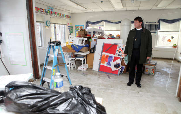 The Rev. Nicholas T. Porter  of Trinity Episcopal Church in Southport, Conn. looks at the damage to the church's nursery school, which took on over four feet of water, on Monday, November 5, 2012. Porter also attended the school as a child. Photo: BK Angeletti, B.K. Angeletti / Connecticut Post freelance B.K. Angeletti
