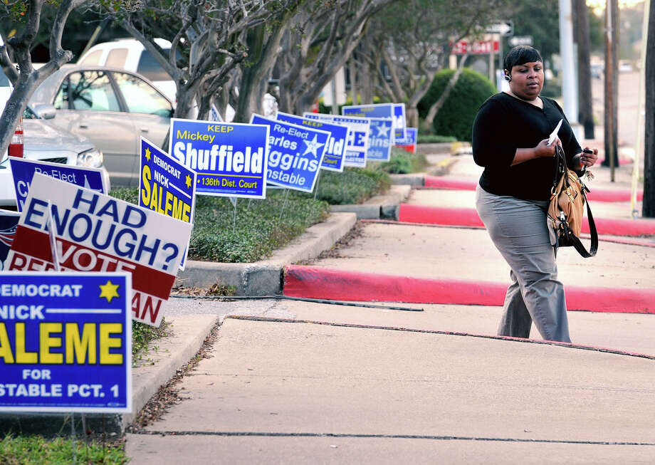 Michelle Bell of Beaumont walks past a row of election signs in front of the Jefferson County Courthouse on Monday. Photo taken Monday, November 06, 2012 Guiseppe Barranco/The Enterprise Photo: Guiseppe Barranco, STAFF PHOTOGRAPHER / The Beaumont Enterprise