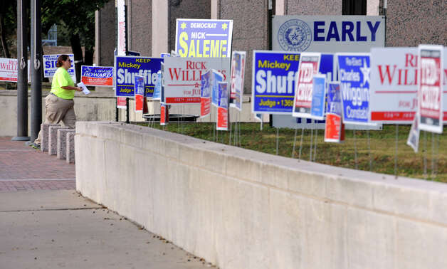 Virginia Rose of Nome walks past a row of election signs in front of the Jefferson County Courthouse on Monday. Photo taken Monday, November 06, 2012 Guiseppe Barranco/The Enterprise Photo: Guiseppe Barranco, STAFF PHOTOGRAPHER / The Beaumont Enterprise
