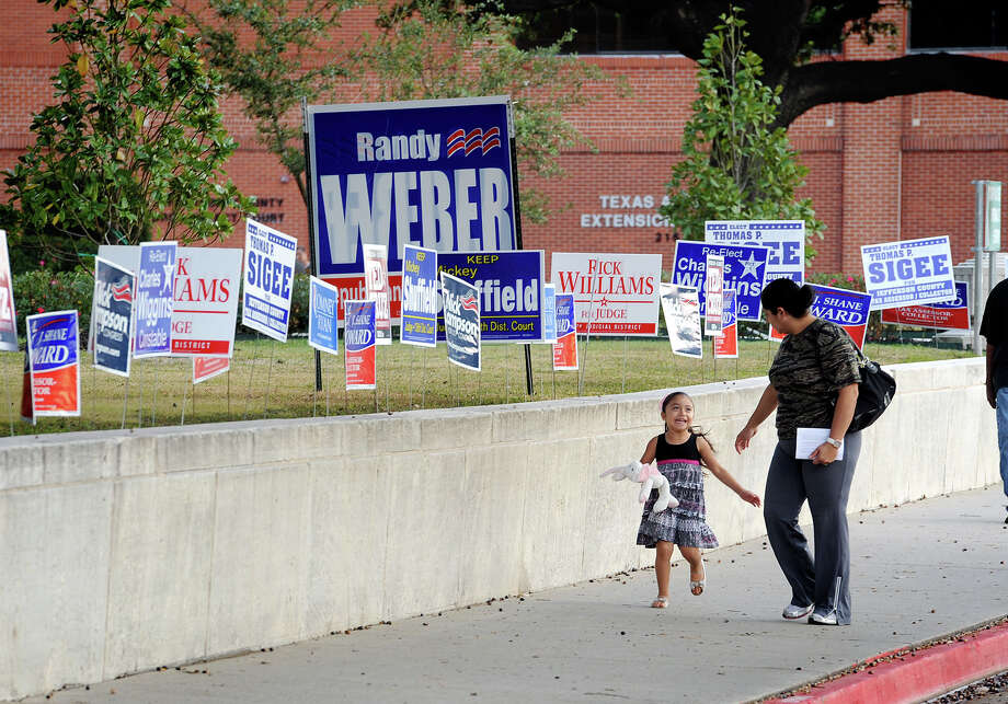Joselyn Mendez, 3, and Abigail Mendez, 29, walk past a row of election signs in front of the Jefferson County Courthouse on Monday. Photo taken Monday, November 06, 2012 Guiseppe Barranco/The Enterprise Photo: Guiseppe Barranco, STAFF PHOTOGRAPHER / The Beaumont Enterprise