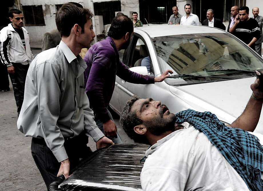 Syrians help a man injured when a car bomb ripped through the main square of a residential neighborhood known as Mazzeh al-Jabal in Damascus, killing 11 people and wounding dozens. Photo: Anonymous, Associated Press