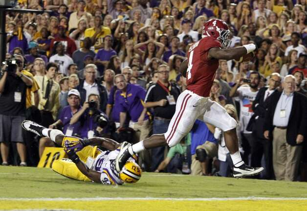 Alabama running back T.J. Yeldon (4) runs over LSU defensive end Barkevious Mingo (49) for the go ahead touchdown to beat LSU 21-17 during the second half of an NCAA college football game on Saturday, Nov. 3, 2012 in Baton Rouge, La.  (AP Photo/Butch Dill) (Associated Press)