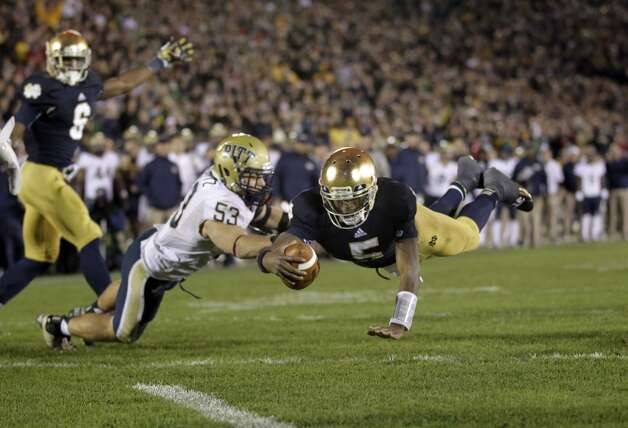Notre Dame quarterback Everett Golson dives into the end zone in front of Pittsburgh linebacker Joe Trebitz for a two-point conversion to tie the game late in the fourth quarter Pittsburgh in an NCAA college football game in South Bend, Ind., Saturday, Nov. 3, 2012. Notre Dame defeated Pittsburgh 29-26 in triple overtime.  (AP Photo/Michael Conroy) (Associated Press)