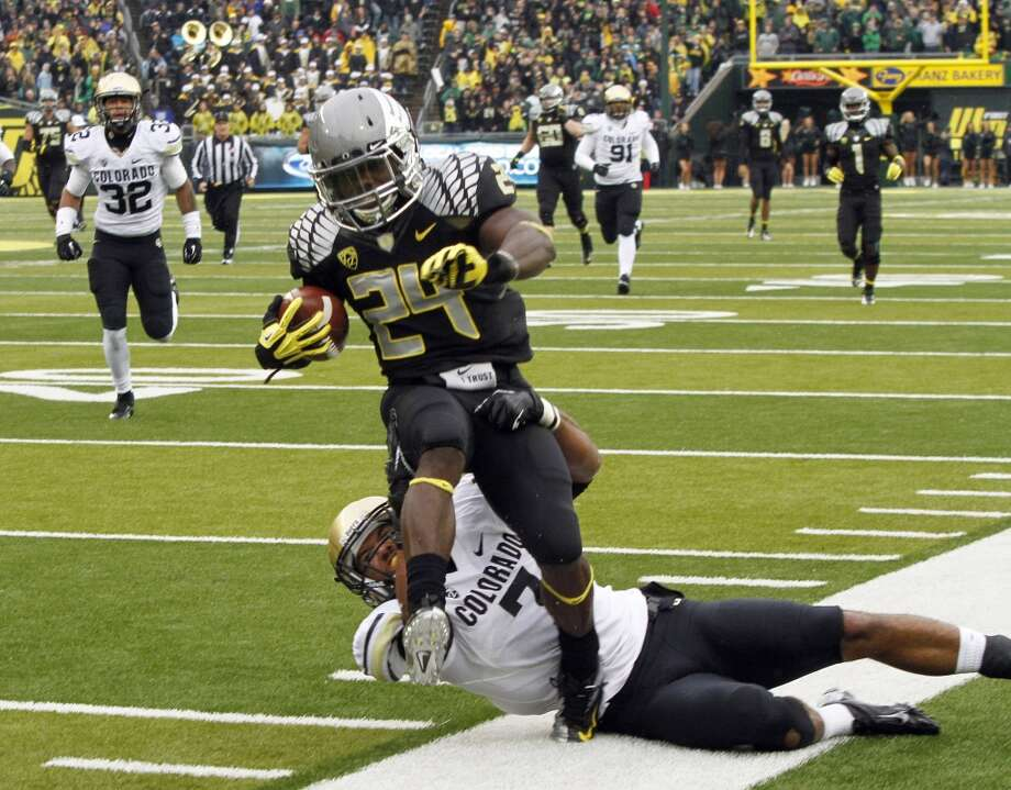 Oregon running back Kenjon Barner (24) is dragged out of bounds by Colorado defender Ray Polk during the first half of an NCAA college football game in Eugene, Ore., Saturday, Oct. 27, 2012. (AP Photo/Don Ryan) (Associated Press)