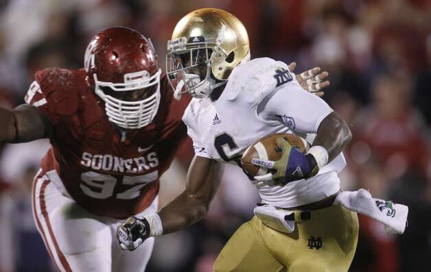 Notre Dame running back Theo Riddick carries past Oklahoma defensive tackle Jamarkus McFarland, rear, on his touchdown run in the fourth quarter of an NCAA college football game in Norman, Okla., Saturday, Oct. 27, 2012. Notre Dame won 30-13. (AP Photo/Sue Ogrocki) (Associated Press)
