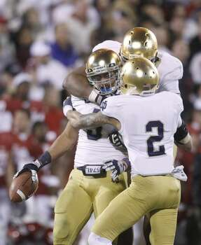 Notre Dame linebacker Manti Te'o, left, celebrates with teammate Stephon Tuitt, right, and Bennett Jackson (2) after an interception against Oklahoma in the fourth quarter of an NCAA college football game in Norman, Okla., Saturday, Oct. 27, 2012. Notre Dame won 30-13. (AP Photo/Sue Ogrocki) (Associated Press)