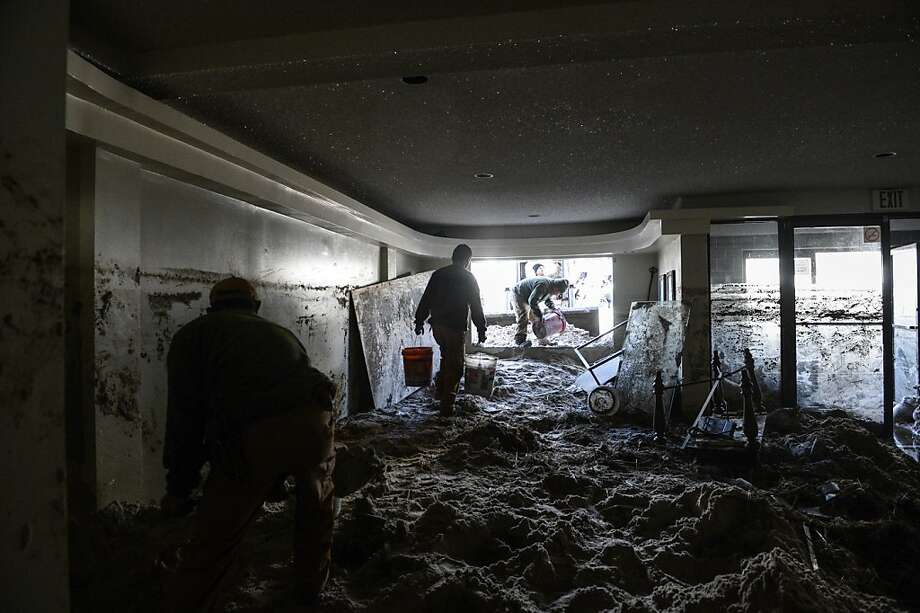 Workers use buckets to clear sand out of the bottom floor of a residence that flooded during Hurricane Sandy in Long Beach, N.Y. Photo: Robert Stolarik, New York Times