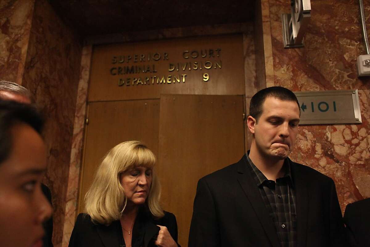 Gregory Graniss (right), stands outside of Department 9 as his attorney speaks with the media.