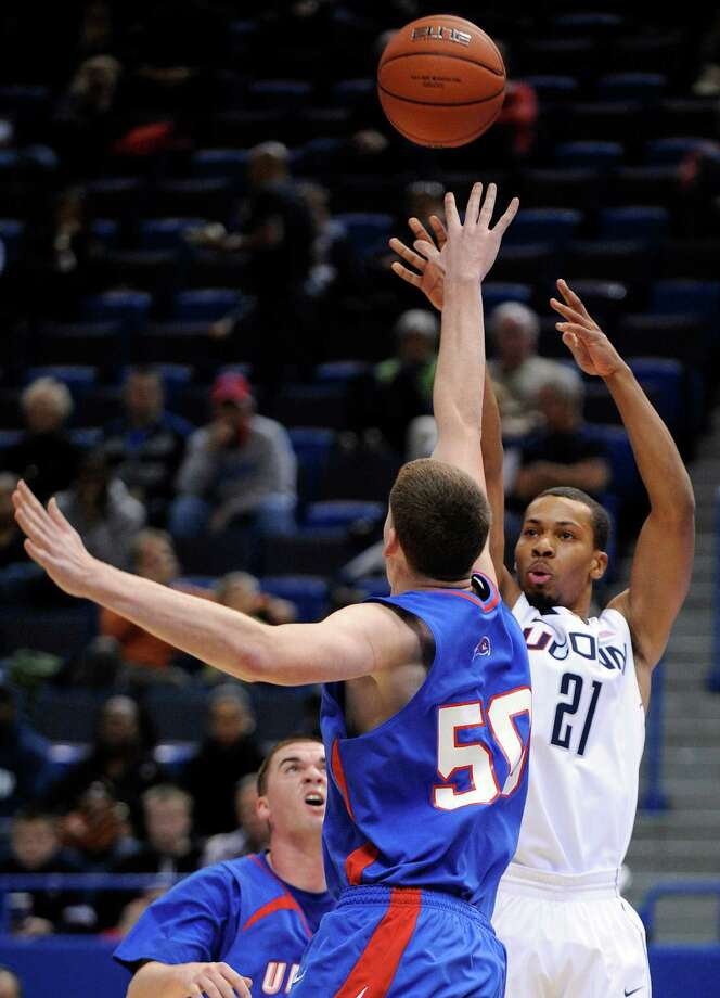 Connecticut's Omar Calhoun, right, scores two of his 20 points while guarded by Massachusetts Lowell's James McDonnell during an exhibition NCAA college basketball game in Hartford, Conn., Sunday, Nov. 4, 2012. Connecticut won the game 100-62. (AP Photo/Fred Beckham) Photo: Fred Beckham, Associated Press / FR153656 AP