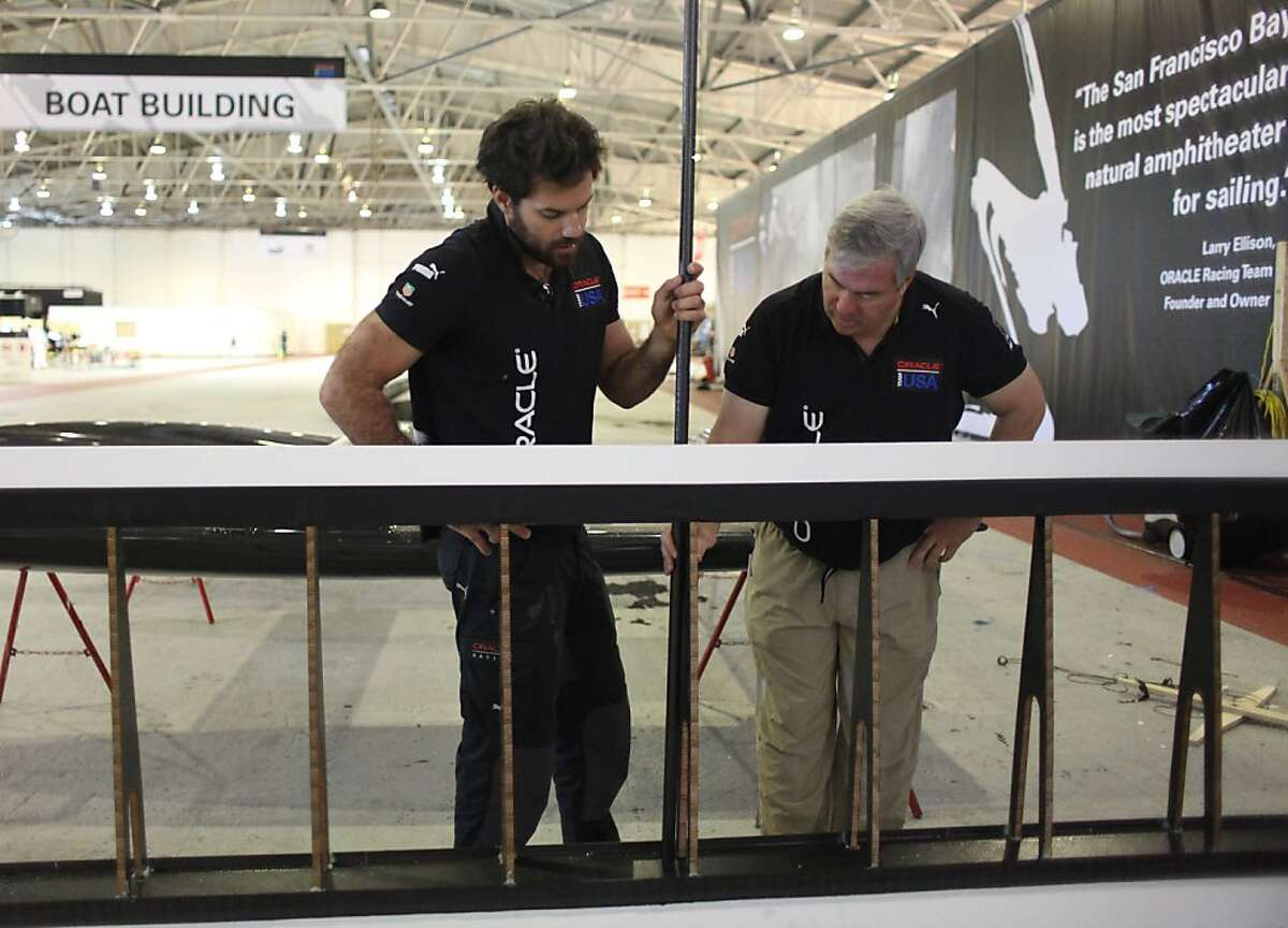 Shannon Falcone (l to r), Oracle Team USA sailing team member, and Tom Speer, Oracle Team USA Aero & Sail Project Leader, stand behind part of a wing salvaged from the Oracle Team USA AC72 boat, which capsized on October 16, 2012, as they discuss the construction of a flying machine for Red Bull Flugtag San Francisco 2012 at the team base on Monday, November 5, 2012 in San Francisco, Calif. The part of the wing salvaged off the AC72 boat will be used on the flying machine being constructed.