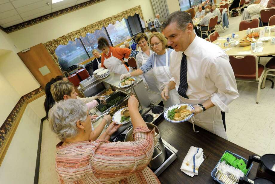 Colin DeMers, right, managing partner at the Century House, waits for volunteer Lettie Saheim to put gravy on the plate as the Century House Restaurant neared its 350,000th meal served at the Cohoes Senior Service Citizen Center as part of its monthly on-site feeding program in Cohoes, NY Thursday Nov. 1, 2012. (Michael P. Farrell/Times Union) Photo: Michael P. Farrell