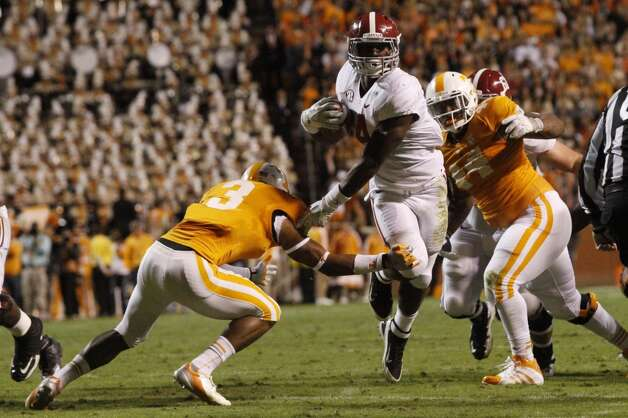 Alabama running back T.J. Yeldon (4) runs as he's hit by Tennessee defensive back Byron Moore (3) during the second quarter of an NCAA college football game on Saturday, Oct. 20, 2012 in Knoxville, Tenn. (AP Photo/Wade Payne) (Associated Press)