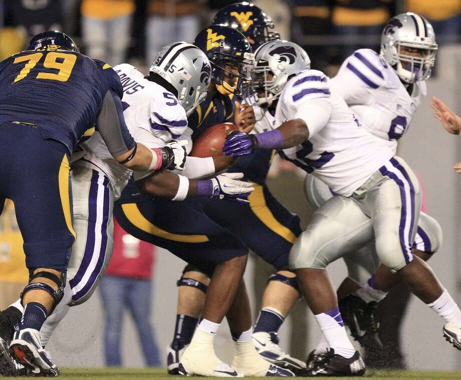 West Virginia quarterback Geno Smith (12) is sacked by Kansas State's Adam Davis (55) and Meshak Williams, right front, during the third quarter of an NCAA college football game in Morgantown, W.Va., Saturday, Oct. 20, 2012. Kansas State won 55-14. (AP Photo/Christopher Jackson) (Associated Press)