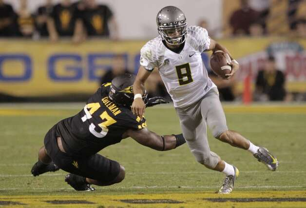 Oregon quarterback Marcus Mariota (8) scrambles for yardage as he is pursued by Arizona State defenders during the first half of an NCAA college football game, Thursday, Oct. 18, 2012, in Tempe, Ariz.  (AP Photo/Matt York) (Associated Press)