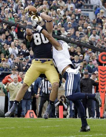 Notre Dame tight end Tyler Eifert , left, makes a catch over BYU defensive back Preston Hadley for a touchdown during the first half of an NCAA college football game in South Bend, Ind., Saturday, Oct. 20, 2012. (AP Photo/Michael Conroy) (Associated Press)