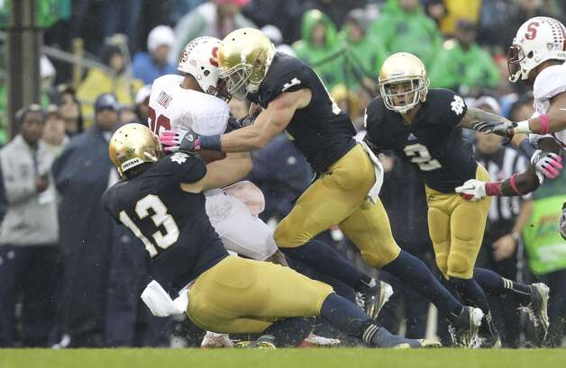 Notre Dame linebacker Danny Spond (13) and safety Zeke Motta (17) tackle Stanford running back Kelsey Young (39) during the first half of an NCAA college football game in South Bend, Ind., Saturday, Oct. 13, 2012. (AP Photo/Nam Y. Huh) (Associated Press)