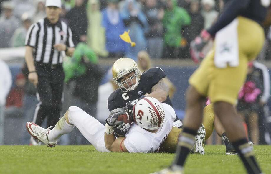 "Notre Dame linebacker Manti Te""o (5), top, tackles as he battles for the ball with Stanford tight end Zach Ertz (86) during the first half of an NCAA college football game in South Bend, Ind., Saturday, Oct. 13, 2012. (AP Photo/Nam Y. Huh) (Associated Press)"