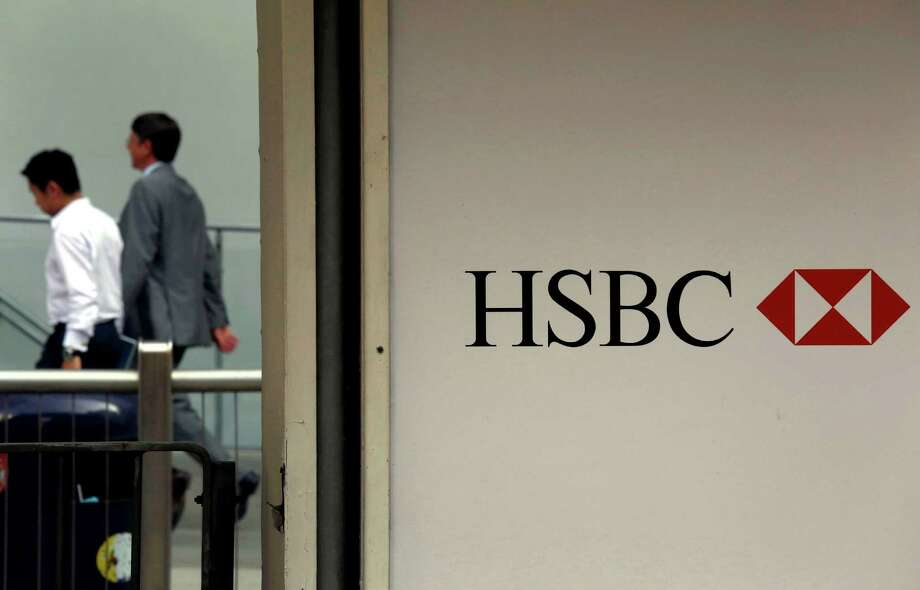 FILE - In this July 30, 2012, file photo, ,People walk past a logo of HSBC headquarters in Hong Kong.  HSBC, Europe's biggest bank, has set aside an additional  $1.15 billion to cover potential U.S. fines for money laundering by its Mexican unit and penalties for mis-selling payment protection insurance. (AP Photo/Vincent Yu, File) Photo: Vincent Yu