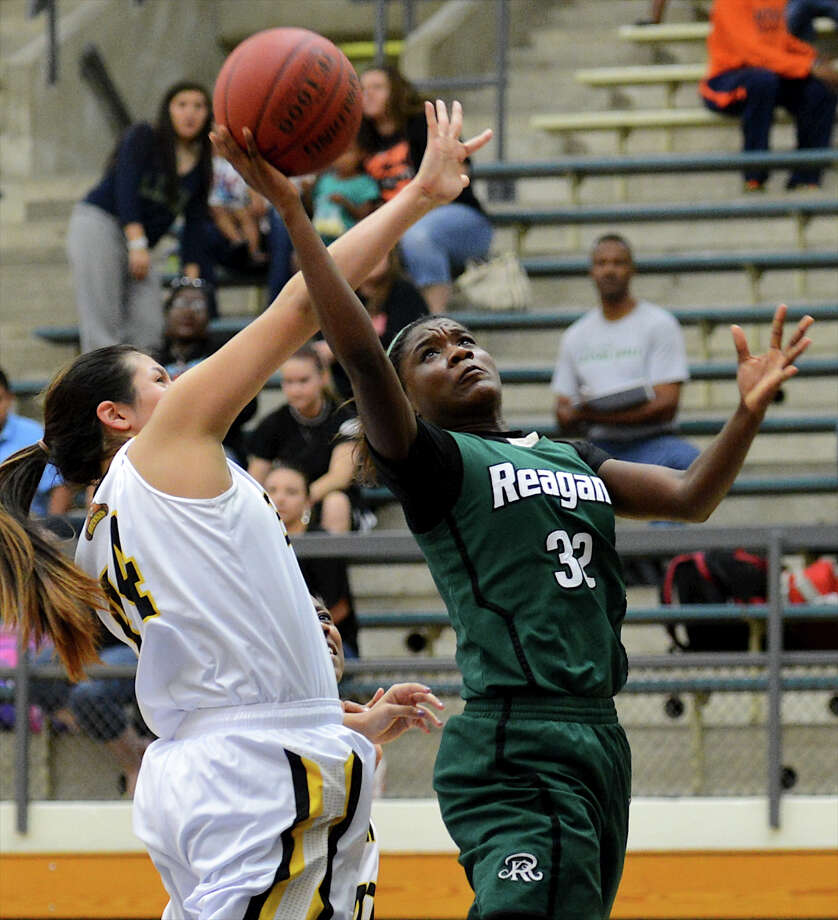 Reagan's Moriah Mack (32) takes a shot past Brennan's Eliza Martinez (44) during a girls non-district basketball game between the Brennan Bears and the Reagan Rattlers at Paul Taylor Field House in San Antonio, Saturday, November 5, 2012.