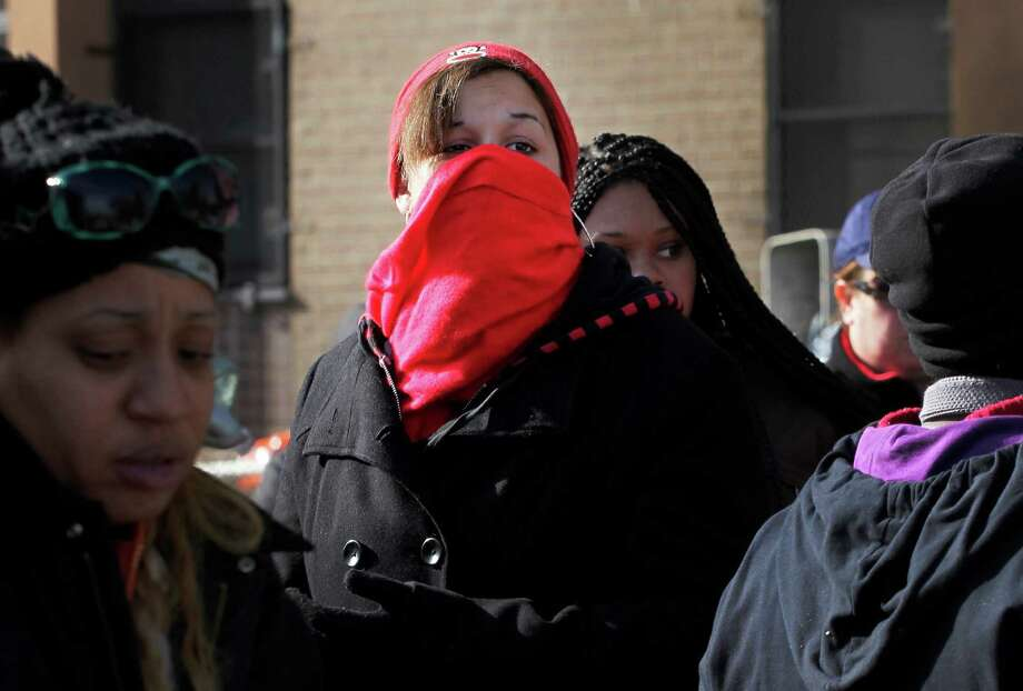 Nicole Vasquez uses a scarf to keep warm while waiting for food at an American Red Cross station in the Coney Island section of Brooklyn, Monday, Nov. 5, 2012 in New York. The region is still cleaning up a week after Superstorm Sandy. (AP Photo/Mark Lennihan) Photo: Mark Lennihan