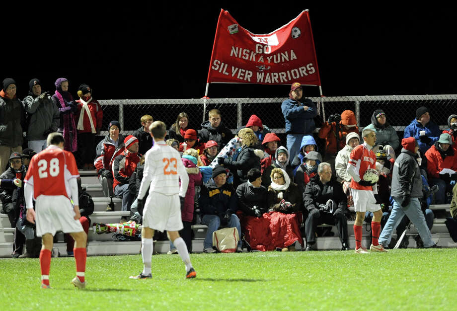 Niskayuna fans try to stay warm on a cold night while watching their team play Bethlehem in the Class AA boy's soccer sectional final on Monday Nov. 5, 2012 in Colonie, N.Y.  (Lori Van Buren / Times Union) Photo: Lori Van Buren
