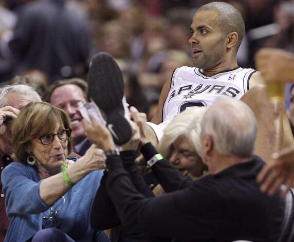 San Antonio Spurs' Tony Parker is helped by fans after landing in their seats while chasing a loose ball during second half action against the Indiana Pacers Monday Nov. 5, 2012 at the AT&T Center. The Spurs won 101-79. (Edward A. Ornelas / San Antonio Express-News)