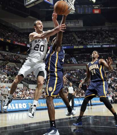 San Antonio Spurs' Manu Ginobili passes around Indiana Pacers' Ian Mahinmi as Indiana Pacers' Paul George looks on during second half action Monday Nov. 5, 2012 at the AT&T Center. The Spurs won 101-79. (Edward A. Ornelas / San Antonio Express-News)