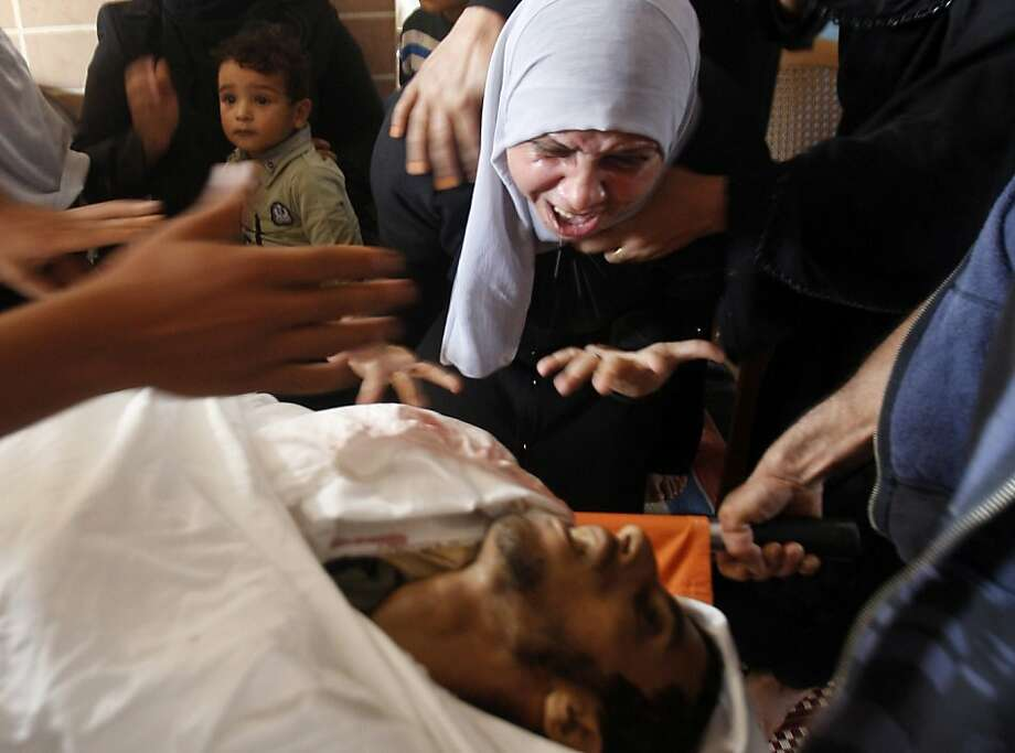 The mother of Palestinian Ahmed Al- Nabahin, 23, grieves over his body during his funeral in the Bureij refugee camp, central Gaza Strip, Monday, Nov. 5, 2012. A Palestinian hospital official says Israeli forces have shot and killed a man at the border fence with the Gaza Strip. It wasn't immediately clear if the man was a civilian. The area is frequently used by militants to fire rockets at nearby Jewish communities, but sometimes others like the mentally disabled enter the area, not understanding its dangers. Photo: Hatem Moussa, Associated Press