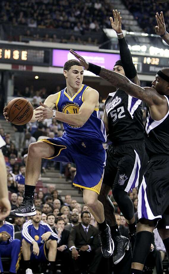 Golden State Warriors guard Klay Thompsopn, left, pass off against Sacramento Kings' James Johnson, center and DeMarcus Cousins, during the first half of an NBA basketball game in Sacramento, Calif., Monday, Nov. 5, 2012. (AP Photo/Rich Pedroncelli) Photo: Rich Pedroncelli, Associated Press