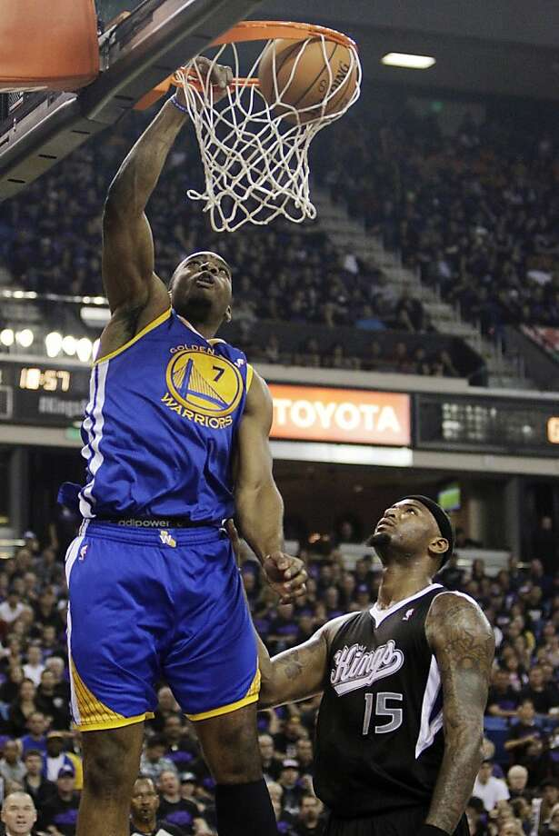 Golden State Warriors forward Carl Landry, left, dunks over Sacramento Kings center DeMarcus Cousins during the first half of an NBA basketball game in Sacramento, Calif., Monday, Nov. 5, 2012. (AP Photo/Rich Pedroncelli) Photo: Rich Pedroncelli, Associated Press