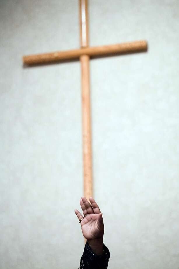 In this  Sunday, Nov. 4, 2012, photo, a woman raises her hand in the air during a speech by David Bullock, the President of Rainbow PUSH Michigan, at the Voter Mobilization Rally at Foss Avenue Baptist Church in Flint, Mich. Photo: Griffin Moores, Associated Press