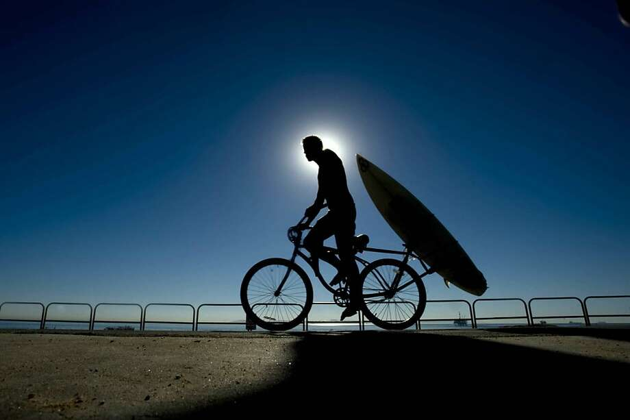 Bike and board: A two-wheeling surfer leaves Dog Beach after catching some waves in Huntington Beach, Calif. Photo: Joshua Sudock, Associated Press