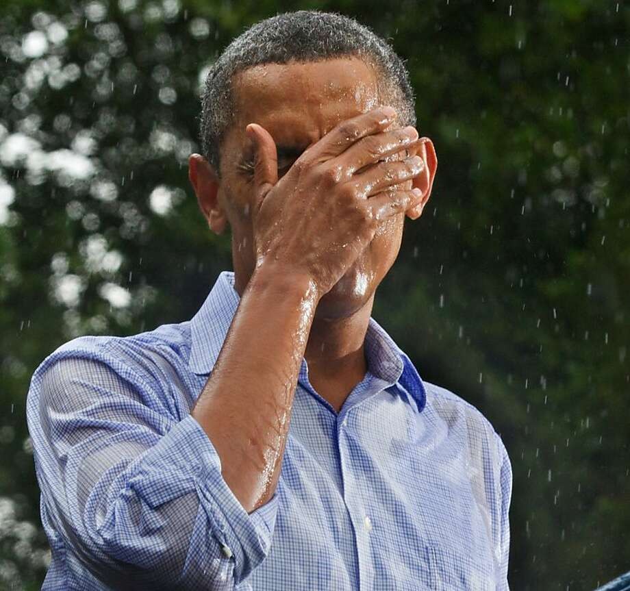 In this July 14, 2012 file photo, President Obama holds a campaign rally despite heavy rain at the historic Walkerton Tavern & Gardens in Glen Allen, Va. (AP Photo/J. Scott Applewhite, File) Photo: J. Scott Applewhite, Associated Press