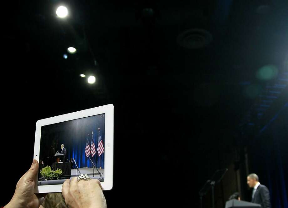 In this Jan. 11, 2012 file photo, an audience member takes a photo of President Obama as he speaks during a campaign event at the University of Illinois in Chicago. (AP Photo/Haraz N. Ghanbari) Photo: Haraz N. Ghanbari, Associated Press