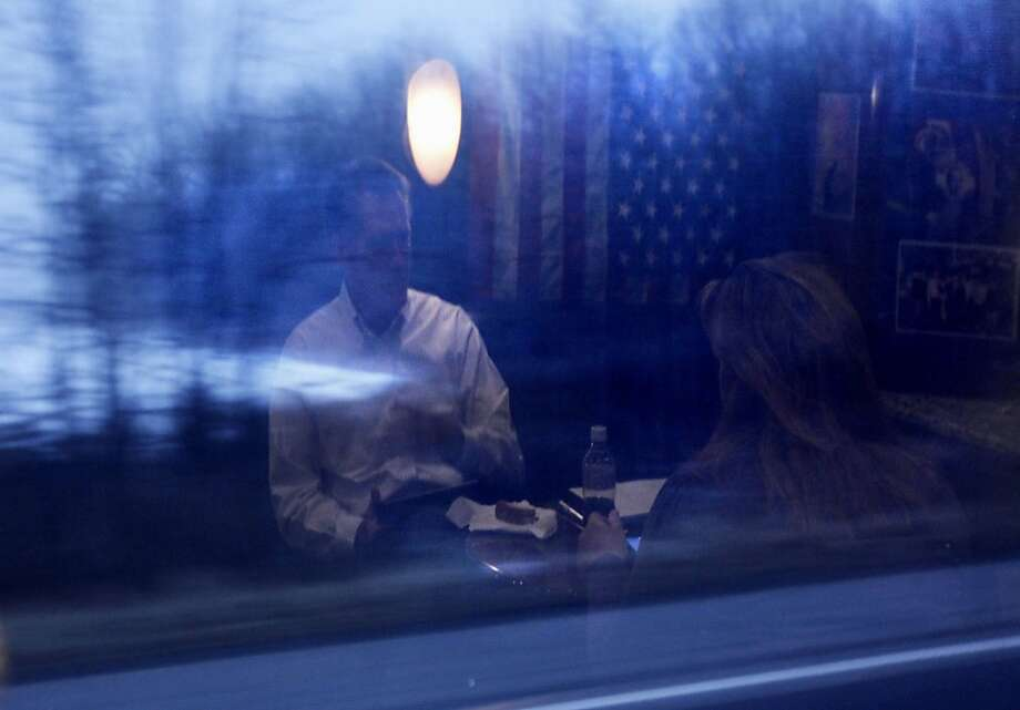 In this Feb. 16, 2012 file photo, Mitt Romney is reflected in a window as he talks with deputy campaign manager Katie Gage on his campaign bus between Monroe, Mich., and Farmington Hills, Mich. (AP Photo/Gerald Herbert, File) Photo: Gerald Herbert, Associated Press