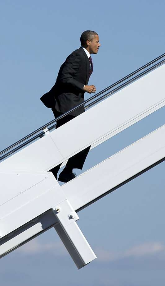 In this Oct. 16, 2012 file photo, President Obama boards Air Force One at Newport News Williamsburg International Airport in Williamsburg, Va., en route to New York. (AP Photo/Carolyn Kaster, File) Photo: Carolyn Kaster, Associated Press