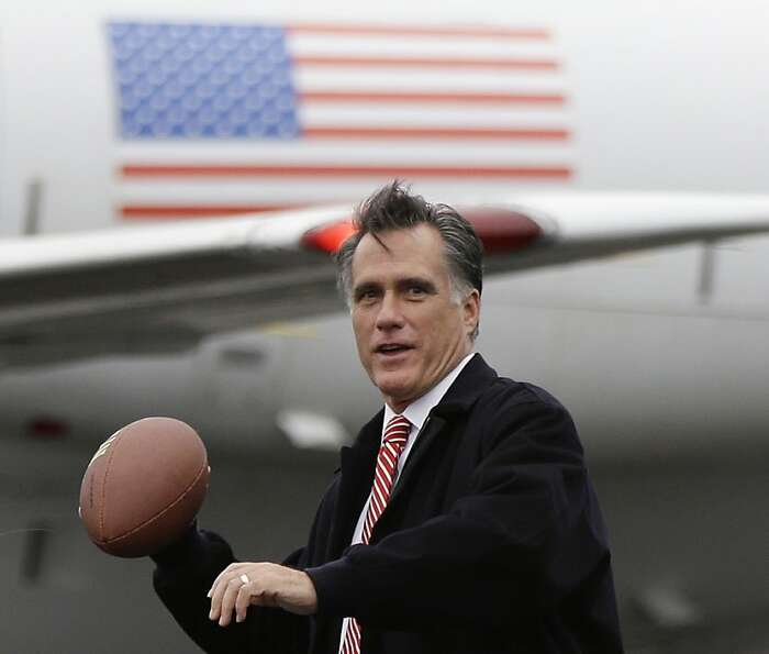 In this Oct. 26, 2012 file photo, Mitt Romney prepares to throw a football on the tarmac of Akron-Ca