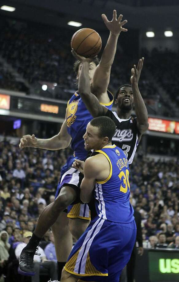 Sacramento Kings  guard Aaron Brooks, center, goes to the basket between  Golden State Warriors' Andrew Bogut, of Australia, left, and Stephen Curry during the closing moments of an NBA basketball game in Sacramento, Calif., Monday, Nov. 5, 2012.  The Kings won 94-92. (AP Photo/Rich Pedroncelli) Photo: Rich Pedroncelli, Associated Press
