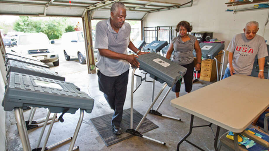 John Martin, Democratic precinct chair and judge of Harris County's Precinct 336, places one of 11 voting machines in it's place with the help of his clerk Jean Fowler in preparation of todays election, Monday, Nov. 5, 2012 in Martin's garage in Houston. Martin and his clerks Jean Fowler, center, and Luis Damian,  right, helped transform his garage into the poling spot. Martin says he opened his garage in 1993 because there wasn't anywhere else to go to vote in the precinct. Martin says turnout early on was slow, however, over 400 people visited the polling site. Martin also said that he has to take a class and get sworn in to serve as the precinct judge. Photo: Nick De La Torre, . / © 2012  Houston Chronicle