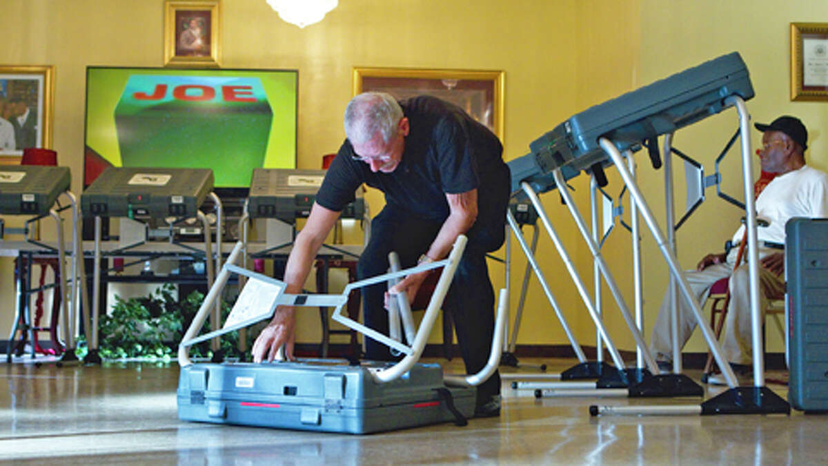 Pete Goedicke, 76, an election clerk, sets up one of the eSlate electronic voting machines at St. Luke's Missionary Baptist Church before election day Monday, Nov. 5, 2012, in Houston.
