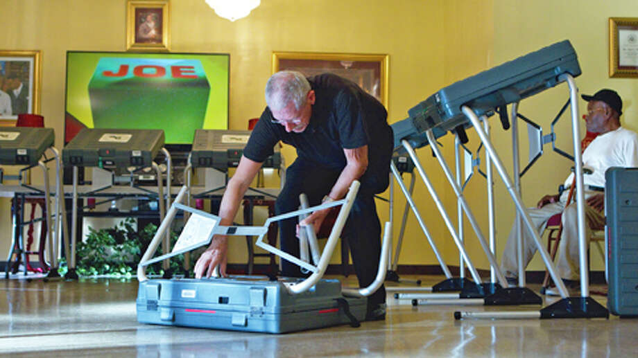 Pete Goedicke, 76, an election clerk, sets up one of the eSlate electronic voting machines at St. Luke's Missionary Baptist Church before election day Monday, Nov. 5, 2012, in Houston. Photo: Johnny Hanson, . / © 2012  Houston Chronicle