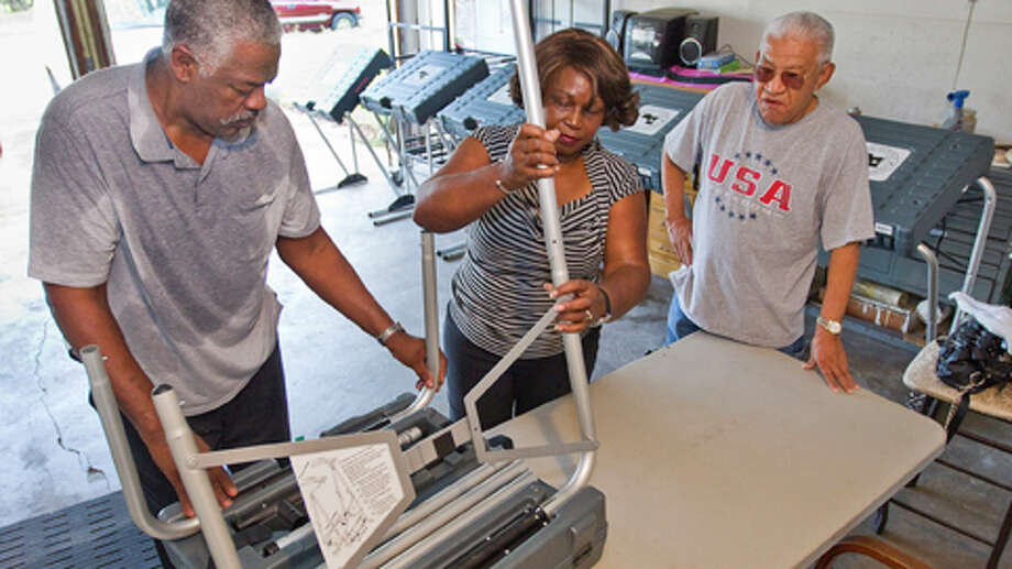 John Martin, Democratic precinct chair and judge of Harris County's Precinct 336, right puts together one of 11 voting machines with the help of his clerk Jean Fowler in preparation of todays election, Monday, Nov. 5, 2012 in Martin's garage in Houston. Luis Damian, right, helps Martin by serving as a clerk. Martin says he opened his garage in 1993 because there wasn't anywhere else to go to vote in the precinct. Martin says turnout early on was slow, however, over 400 people visited the polling site. Martin also said that he has to take a class and get sworn in to serve as the precinct judge. Photo: Nick De La Torre, . / © 2012  Houston Chronicle